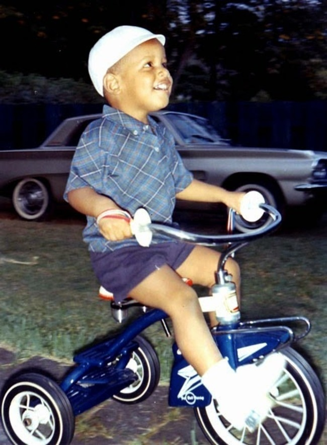 Barack Obama riding a tricycle at age four.